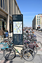 Bikes and tourist map by Cambridge Station, UK March 2018