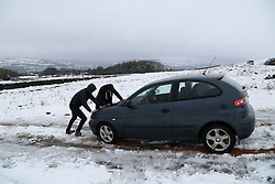 © Licensed to London News Pictures.04/03/16. Ilkley, UK.  Two teenagers in Ilkley try to push their car clear after it became stranded following heavy snowfall over night in Yorkshire caused chaos on many roads. Forecasters are predicting more cold weather this week as Storm Jake takes hold. Photo credit : Ian Hinchliffe/LNP