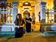 30 MARCH 2018 - BANGKOK, THAILAND: Women kneel on the pavement and pray during the Stations of the Cross procession during Good Friday observances at Santa Cruz Church in the Thonburi section of Bangkok. Santa Cruz Church is more than 350 years old and is one of the oldest Catholic churches in Thailand. Good Friday is the day that most Christians observe as the crucifixion of Jesus Christ. Thailand has a small Catholic community.        PHOTO BY JACK KURTZ