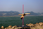 YICHANG, CHINA - MARCH 11: (CHINA OUT) <br /> <br /> Pole Dancing Training In Yichang<br /> <br /> A pole dancer performs by the riverside of Yangtze River on March 11, 2016 in Yichang, Hubei Province of China. It\'s said that the performance comes from several pole dance enthusiasts who organized training to promote pole dancing. <br /> ©Exclusivepix Media