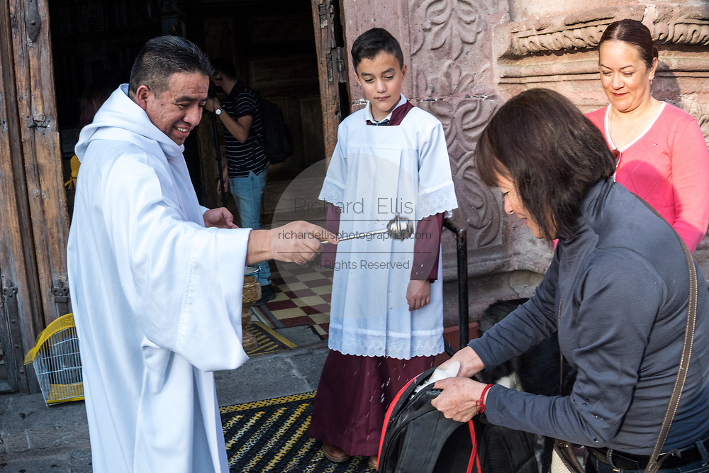 A Roman Catholic priest blesses pets and their owners during the annual blessing of the animals on the feast day of San Antonio Abad at Oratorio de San Felipe Neri church January 17, 2020 in the historic center of San Miguel de Allende, Guanajuato, Mexico.
