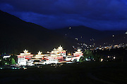 Tashichoi Dzong at night, the seat of government and spiritual Buddhism with the capital Thimpu behind...Bhutan the country that prides itself on the development of 'Gross National Happiness' rather than GNP. This attitude pervades education, government, proclamations by royalty and politicians alike, and in the daily life of Bhutanese people. Strong adherence and respect for a royal family and Buddhism, mean the people generally follow what they are told and taught. There are of course contradictions between the modern and tradional world more often seen in urban rather than rural contexts. Phallic images of huge penises adorn the traditional homes, surrounded by animal spirits; Gross National Penis. Slow development, and fending off the modern world, television only introduced ten years ago, the lack of intrusive tourism, as tourists need to pay a daily minimum entry of $250, ecotourism for the rich, leaves a relatively unworldly populace, but with very high literacy, good health service and payments to peasants to not kill wild animals, or misuse forest, enables sustainable development and protects the country's natural heritage. Whilst various hydro-electric schemes, cash crops including apples, pull in import revenue, and Bhutan is helped with aid from the international community. Its population is only a meagre 700,000. Indian and Nepalese workers carry out the menial road and construction work.