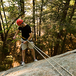 A man rappelling over Lower Slab in New Hampshire's Pawtuckaway State Park.