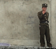 A North Korean soldier smokes a cigarette on a pier in the town of Sunuiju October 10, 2006.  DPRK, north korea, china, dandong, border, liaoning, democratic, people's, rebiblic, of, korea, nuclear, test, rice, japan, arms, race, weapons, stalinist, communist, kin jong il