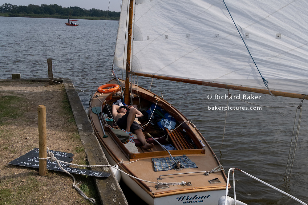 A sailor takes a mid-day nap on his yacht at Hickling Broad, on 11th August 2020, in Hickling, Norfolk, England.
