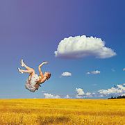 Girl falling in blue cloudy sky over a yellow summer field