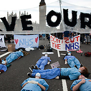 Activists dressed as health workers playing dead..The Health and Care Bill has been passed by Parliament and is due to go to the House of Lords. In protest against the bill which aim to deconstruct and privatise large parts of the NHS UK Uncut activists together with health workers and trade unionists blocked the Westminster Bridge from 1pm til 5.30pm.