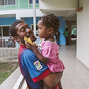 INDIVIDUAL(S) PHOTOGRAPHED: Donald Michel (left) and Naydoulie Michel (right). LOCATION: St. Damien Hospital, Nos Petits Frères et Sœurs, Tabarre 41 Commune, Haïti. CAPTION: A young father, Donald Michel, is waiting for the delivery of medicine for his two-year-old girl, Naydoulie, at the pharmacy of St. Damien Hospital.