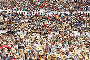 Crowds pack the bleachers and wave their hats calling out for gifts at the Guelaguetza Auditorium on Cerro del Fortin in Oaxaca City, Oaxaca, Mexico on July 21, 2008. The Guelaguetza is an annual folk dance festival in Oaxaca - dancers from different regions of the state gather in celebration in Oaxaca City and towns in the Central Valley to perform their regional dances wearing traditional costumes and throw regional specialties as gifts into the crowds.