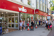 Shoppers line up waiting to enter Wilko in Folkestone town centre on the 15th of June 2020, the day the shops re-open for the first time in 3 months, Folkestone, United Kingdom. Some essential business's including Wilko that sell food and cleaning products continued operating during the Corona virus outbreak but still have strict health guidelines regarding COVID-19 for all people entering the premises regarding social distancing.