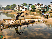 """01 MARCH 2014 - MAE SOT, TAK, THAILAND: A Burmese boy fishes on a temporary footbridge to a boat landing in the Moie River in Mae Sot. Boats from Myawaddy, Myanmar (the buildings in the background are in Myawaddy) drop and pick up passengers for the short trip across the river. Mae Sot, on the Thai-Myanmar (Burma) border, has a very large population of Burmese migrants. Some are refugees who left Myanmar to escape civil unrest and political persecution, others are """"economic refugees"""" who came to Thailand looking for work and better opportunities.    PHOTO BY JACK KURTZ"""