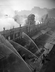 Smoke and steam rise in white clouds as jets of water are directed through the empty windows into the shell of the Union Cold Storage Company at Smithfield Market, London.