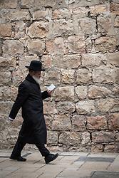 23 February 2020, Jerusalem: A Jewish man walks down a road in the Jerusalem Old City, reading.