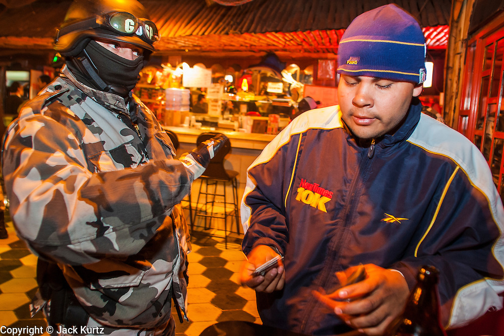 """05 FEBRUARY 2005 - NOGALES, SONORA, MEXICO: Nogales, Mexico, police talk to people in a bar in Nogales during an anti-gang sweep. Members of """"Grupo Operativos"""" a special operations unit of the Nogales, Sonora, Mexico, police department, on patrol in Nogales, Saturday night, Feb. 5. The Operativos specialize in anti-gang enforcement and drug interdiction missions. In recent months they have stepped up patrol activity in Nogales communities near the border. In January 2005, the US Department of State has issued a travel advisory advising US citizens to avoid travel along the US Mexican border because of increased violence, including the kidnapping of US citizens, in border communities. Most of the violence has been linked to the drug cartels, who are increasingly powerful in Mexico. The Operativos also patrol the districts of Nogales frequented by US tourists in an effort to prevent crime directed against US citizens.   PHOTO BY JACK KURTZ"""
