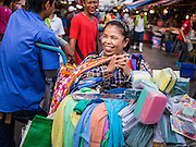 "05 APRIL 2014 - BANGKOK, THAILAND:   An apron vendor Khlong Toey Market in Bangkok. Khlong Toey (also called Khlong Toei) Market is one of the largest ""wet markets"" in Thailand. The market is located in the midst of one of Bangkok's largest slum areas and close to the city's original deep water port. Thousands of people live in the neighboring slum area. Thousands more shop in the sprawling market for fresh fruits and vegetables as well meat, fish and poultry.     PHOTO BY JACK KURTZ"