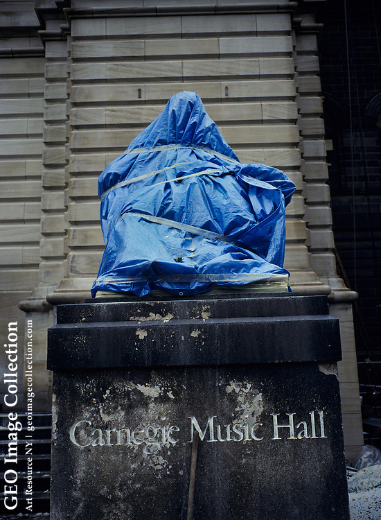 Wrapped statue of Shakespeare on a pedestal at entrance to the Carnegie Music Hall. The statue is wrapped as protection during cleaning process for the building.