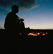 A man photographs a lava flow in Hawaii Volcanoes National Park, Hawaii, USA