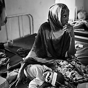 24-year-old Fatima Gedi is seen with her malnutrioned one year old son, Mubaraq inside the stabilization ward of the GIZ Main Hospital in the Dadaab refugee camp in northeastern Kenya. Hundreds of thousands of refugees are fleeing lands in Somalia due to severe drought and arriving in what has become the world's largest refugee camp. Photo: Sanjit Das/Panos
