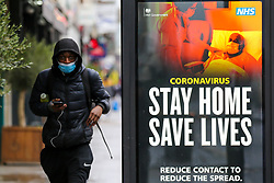 "© Licensed to London News Pictures. 12/01/2021. London, UK. A man wearing a protective face covering walks past the government's 'Stay Home, Save Lives' Covid-19 publicity campaign poster in north London, as the number of cases of the mutated variant of the SARS-Cov-2 virus continues to spread around the country. The message in the advertising campaign says, 'reduce contact to reduce the spread' and Prime Minister Boris Johnson has said that the public should ""stay at home"". Photo credit: Dinendra Haria/LNP"