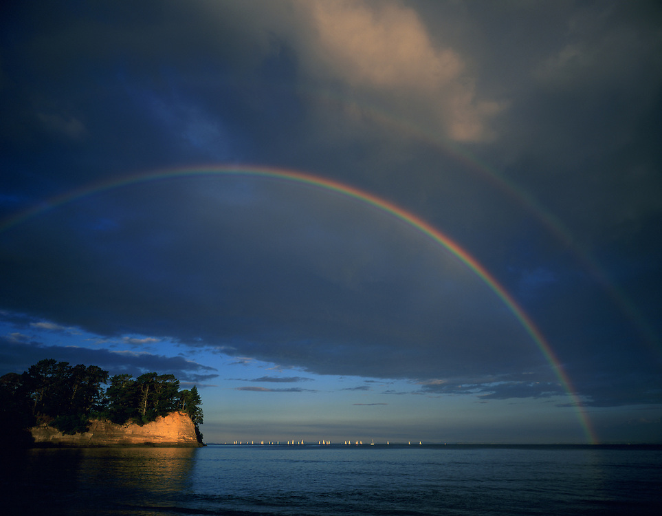 Rainbow glows above the Hauraki Gulf near Auckland New Zealand with a regatta of sailboats on the water.