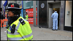 Police Officers outside the Foot Locker store in  Oxford Street after an 18 year old  boy was stabbed to death Oxford Street, central London, on Boxing Day, during the Boxing Day Sales Tuesday December 27, 2011. Photo By Andrew Parsons/i-Images