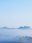 A villa sits on a hilltop, visible above a thick morning mist near Montalcino, Tuscany, Italy