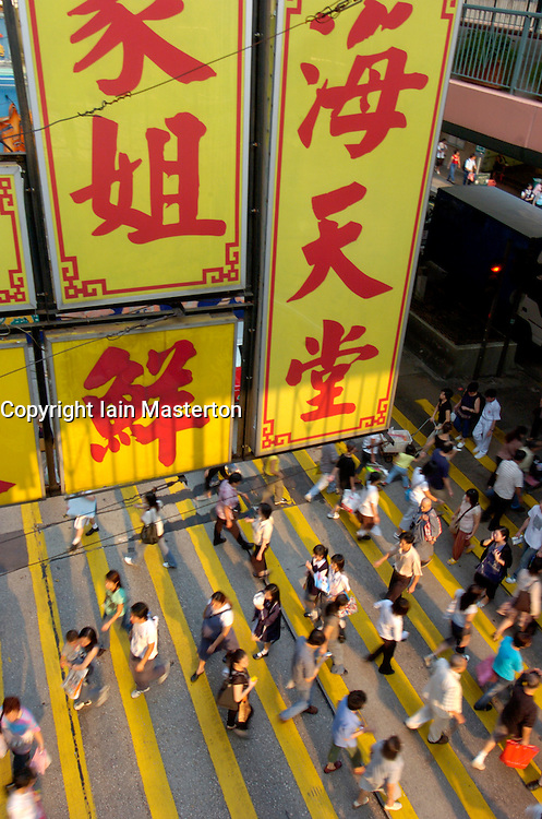 Pedestrians cross street below large billboard in Hong Kong China