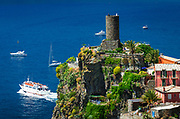 Doria Castle and tour boat leaving the town of Vernazza, Cinque Terre, Liguria, Italy