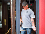 31 MAY 2020 - DES MOINES, IOWA: FRANK SINGLETON, from Elite Glass and Metal, takes measurements for a new window in front of Spaghetti Works, a popular restaurant in downtown Des Moines, after rioters shattered the windows. A group of rioters, protesting the death of George Floyd in police custody in Minneapolis, smashed windows in businesses and restaurants around the Polk County Courthouse in Des Moines. Des Moines police said they made 25 arrests Saturday night and very early Sunday morning. No one was hurt in the disturbances.     PHOTO BY JACK KURTZ