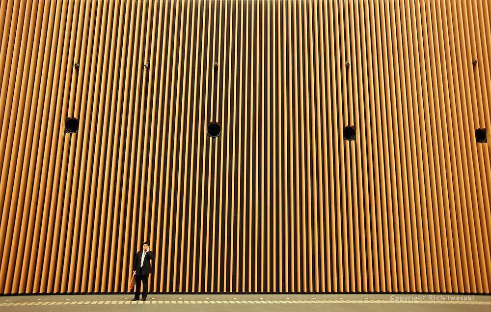 Businessman talks on cell phone near interior wall of Tokyo International Forum building, Yurakucho district, Tokyo, Japan