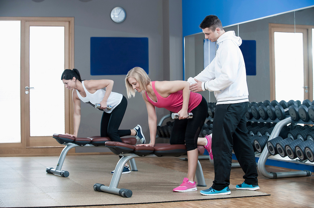 Coach supporting two women in gym doing weight training