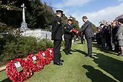 Officials from Japan lay wreaths of poppies at the Cross of Sacrifice during the Remembrance Sunday ceremony at the Hodogaya, Commonwealth War Graves Cemetery in Hodogaya, Yokohama, Kanagawa, Japan. Sunday November 11th 2018. The Hodagaya Cemetery holds the remains of more than 1500 servicemen and women, from the Commonwealth but also from Holland and the United States, who died as prisoners of war or during the Allied occupation of Japan. Each year officials from the British and Commonwealth embassies, the British Legion and the British Chamber of Commerce honour the dead at a ceremony in this beautiful cemetery. The year 2018 marks the centenary of the end of the First World War in 1918.