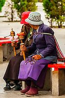 Tibetan pilgrims sitting near the Potala Palace, Lhasa, Tibet (Xizang), China.