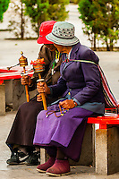 Tibetan pilgrims sitting near the Potala Palace, Lhasa, Tibet (Xizang), China.