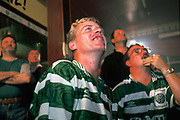 Celtic fans watch their team on television in a pub close to at Parkhead, Glasgow.