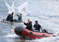 © Licensed to London News Pictures. 15/06/2016. London, UK. Brendan Cox (right), husband of Labour MP Jo Cox, drives an 'IN' campaign protest boat as Nigel Farage leads a flotilla of pro-Brexit fishing boats down the River Thames. Jo Cox MP died on Thursday 16 June 2016 after being shot and stabbed in Birstall, Leeds. Her husband has urged people to 'fight against the hatred' that killed his wife. Photo credit: Rob Pinney/LNP