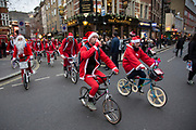 Members of Old School BMX Life on the Santa Cruise charity day out in Soho, London, UK. All dressed up wearing Santa Claus outfits and sporting fine white beards, while riding their beloved BMXs. A fun gathering for friends and enthusiasts to celebrate Christmas.