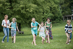 Group of children competing in an egg-and-spoon race in park, Munich, Bavaria, Germany