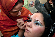 Afghanistan. Herat Women's prison - beauty class. A woman prisoner learns to apply eye make-up