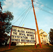 During a journey into America's hinterlands, days after the September 11th attacks in New York and Washington DC, a sign spelling out a message of faith and patriotism is seen outside the Upper Seneca Baptist church in Cedar Grove, Maryland. The preacher has written God Bless America but has misspelled 'devastation' that the Devil is bringing. Messages and slogans appeared all over America following the trauma and the desire for retribution following the terrorist attacks that killed thousands, Christians wanted reprisals as emotions ran high in the media. Small community churches preached against Islam in the same breath as the Devil's evil. The rhetoric of the Crusades as said by President Bush was also a popular way of stirring the propaganda for invasion and war.