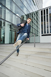 Happy teenagers holding the laptop and jumping railing after work, Bavaria, Germany