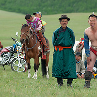 MONGOLIA. After watching a traditional horse race ridden by children such as those in the background, a nomadic herder crouches beside judge as he prepares to wrestle at a naadam festival on a remote pass in Arbulag Sum, near Muren in Hovsgol Aimag, Mongolia. This ancient sport is immensely popular across the country, and legend says that men wear their unique costumes to prove that they are not women, after a woman once humiliated male wrestlers by beating them.  The motorcycle is a sign of rapidly changing times for these herders.