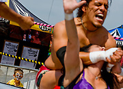 A young wrestlemania fan watches the action in the ring between Kaos, top, and Jezabel at the Volcomania World Championship surfing competition in Newport Beach, CA.