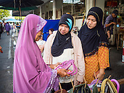 18 JUNE 2015 - PATTANI, PATTANI, THAILAND: Women buy purses and socialize in the market in Pattani. Many Thai Muslims go shopping early in the day to buy food for Iftar, the meal that breaks the day long Ramadan fast.    PHOTO BY JACK KURTZ