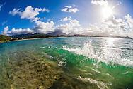 Wave breaking off Popoia Island (Flat Island), Kailua Beach Park and the Koolau Mountains in the background. Kailua Bay, Oahu, Hawaii