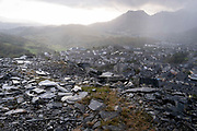 Tons of wasted slate is seen above the town of Blaenau Ffestiniog, on 2nd October 2021, in Blaenau Ffestiniog, Gwynedd, Wales. The derelict slate mines around Blaenau Ffestiniog in north Wales were awarded UNESCO World Heritage status in 2021. The industry's heyday was the 1890s when the Welsh slate industry employed approximately 17,000 workers, producing almost 500,000 tonnes of slate a year, around a third of all roofing slate used in the world in the late 19th century. Only 10% of slate was ever of good enough quality and the surrounding mountains now have slate waste and the ruined remains of machinery, workshops and shelters have changed the landscape for square miles.