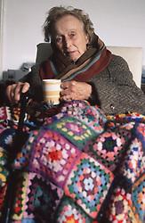 Elderly woman wrapped in blanket holding mug of tea,