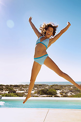 Smiling Young Woman Jumping Mid-air by Swimming Pool