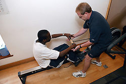 Access to services,  Fitness instructor and disabled man in the gym; using Rowing Machine,