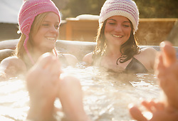 Two smiling young women relaxing in a hot tub apres-ski